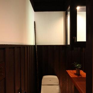 Mittelgroße Urige Gästetoilette mit Toilette mit Aufsatzspülkasten, weißer Wandfarbe, braunem Holzboden, freigelegten Dachbalken und vertäfelten Wänden in Tokio Peripherie
