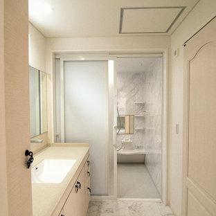 他の地域のシャビーシック調のおしゃれなトイレ・洗面所 (フラットパネル扉のキャビネット、白いキャビネット、白い壁、大理石の床、一体型シンク、グレーの床) の写真