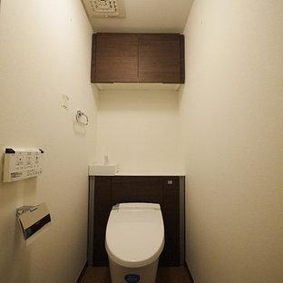 Неиссякаемый источник вдохновения для домашнего уюта: туалет в классическом стиле с коричневыми фасадами, белыми стенами, пробковым полом и коричневым полом