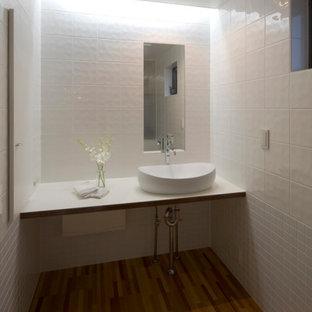 他の地域の小さいモダンスタイルのおしゃれなトイレ・洗面所 (フラットパネル扉のキャビネット、白いキャビネット、一体型トイレ、白いタイル、セラミックタイル、白い壁、合板フローリング、ベッセル式洗面器、ラミネートカウンター、茶色い床、白い洗面カウンター、造り付け洗面台、塗装板張りの天井) の写真