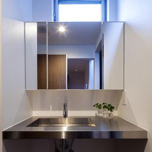 Foto di un bagno di servizio industriale con lavabo sottopiano e top in acciaio inossidabile