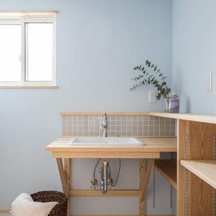 他の地域の北欧スタイルのおしゃれなトイレ・洗面所 (オープンシェルフ、淡色木目調キャビネット、青い壁、オーバーカウンターシンク、木製洗面台、グレーの床、ベージュのカウンター) の写真