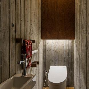 Imagen de aseo industrial con paredes grises, suelo de madera en tonos medios, suelo marrón, armarios con paneles lisos y puertas de armario de madera oscura