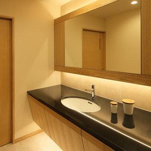 На фото: туалет в восточном стиле с плоскими фасадами, фасадами цвета дерева среднего тона, бежевыми стенами, накладной раковиной и бежевым полом с