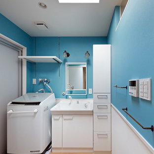大阪の北欧スタイルのおしゃれなトイレ・洗面所 (レイズドパネル扉のキャビネット、白いキャビネット、青い壁、淡色無垢フローリング、一体型シンク、ベージュの床、白い洗面カウンター) の写真