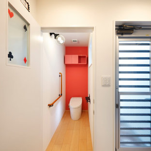 大阪の北欧スタイルのおしゃれなトイレ・洗面所 (赤い壁、淡色無垢フローリング、ベージュの床) の写真