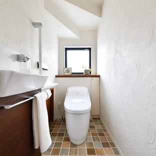 На фото: туалет в скандинавском стиле с плоскими фасадами, коричневыми фасадами, белыми стенами, настольной раковиной и коричневым полом