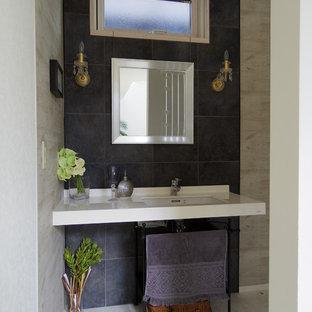 На фото: туалет в стиле модернизм с керамогранитной плиткой, серыми стенами, полом из фанеры, подвесной раковиной, белым полом и белой столешницей с