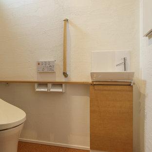 Idées déco pour un WC et toilettes moderne avec un mur blanc et un sol en liège.