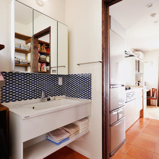 Imagen de aseo asiático con armarios abiertos, paredes blancas, suelo de baldosas de terracota, lavabo integrado, suelo naranja y encimeras blancas