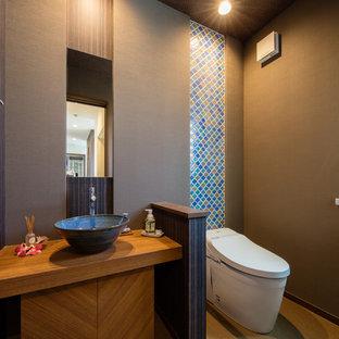 東京23区の広いトラディショナルスタイルのおしゃれなトイレ・洗面所 (家具調キャビネット、濃色木目調キャビネット、一体型トイレ、青いタイル、モザイクタイル、コンソール型シンク、ベージュの床、グレーの壁) の写真