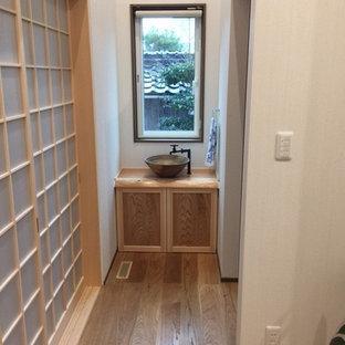 Modelo de aseo de estilo zen, de tamaño medio, con armarios con rebordes decorativos, puertas de armario de madera clara, sanitario de una pieza, baldosas y/o azulejos multicolor y encimera de madera