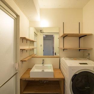 Пример оригинального дизайна: туалет в современном стиле с унитазом-моноблоком, белыми стенами, полом из линолеума, настольной раковиной, столешницей из дерева и серым полом