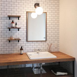 他の地域の小さいミッドセンチュリースタイルのおしゃれなトイレ・洗面所 (白いタイル、サブウェイタイル、白い壁、セラミックタイルの床、オーバーカウンターシンク、黒い床、ブラウンの洗面カウンター、オープンシェルフ、ヴィンテージ仕上げキャビネット、木製洗面台) の写真