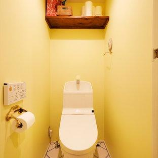 Réalisation de WC et toilettes design avec un mur jaune, un sol multicolore et un carrelage jaune.