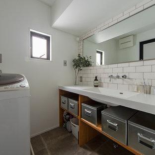 大阪の中くらいのインダストリアルスタイルのおしゃれなトイレ・洗面所 (オープンシェルフ、中間色木目調キャビネット、白いタイル、サブウェイタイル、白い壁、一体型シンク、人工大理石カウンター、グレーの床、白い洗面カウンター) の写真