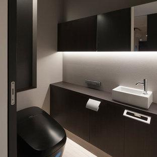 東京都下のモダンスタイルのおしゃれなトイレ・洗面所 (フラットパネル扉のキャビネット、黒いキャビネット、マルチカラーの壁、ベッセル式洗面器、ベージュの床) の写真