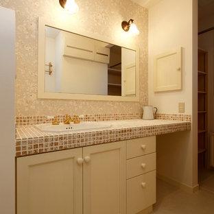 他の地域のカントリー風おしゃれなトイレ・洗面所 (落し込みパネル扉のキャビネット、白いキャビネット、マルチカラーの壁、オーバーカウンターシンク、タイルの洗面台) の写真