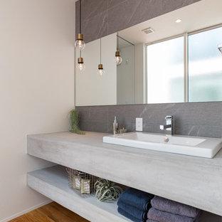 Diseño de aseo moderno con armarios abiertos, puertas de armario grises, baldosas y/o azulejos grises, paredes blancas, suelo de madera en tonos medios, lavabo encastrado, encimera de cemento, suelo marrón y encimeras grises