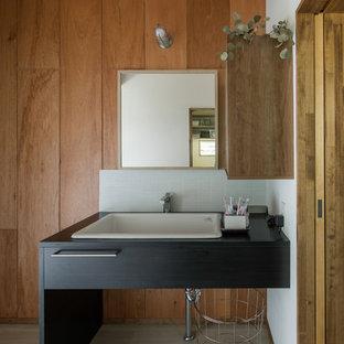 他の地域のインダストリアルスタイルのおしゃれなトイレ・洗面所 (茶色い壁、塗装フローリング、オーバーカウンターシンク、グレーの床、黒い洗面カウンター) の写真