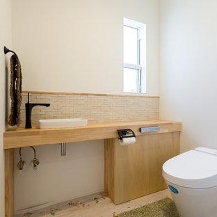 他の地域の北欧スタイルのおしゃれなトイレ・洗面所 (白い壁、淡色無垢フローリング、ベッセル式洗面器、フラットパネル扉のキャビネット、淡色木目調キャビネット、壁掛け式トイレ、ベージュのタイル、木製洗面台) の写真