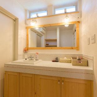 Ejemplo de aseo de estilo zen con armarios con paneles empotrados, puertas de armario de madera oscura, paredes blancas, suelo de madera en tonos medios, lavabo encastrado, encimera de azulejos y suelo marrón