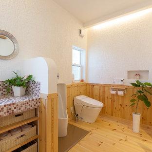 Modelo de aseo asiático con armarios abiertos, paredes blancas, suelo de madera en tonos medios, encimera de azulejos y suelo marrón