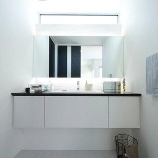 他の地域のモダンスタイルのおしゃれなトイレ・洗面所 (フラットパネル扉のキャビネット、白いキャビネット、白い壁、オーバーカウンターシンク、グレーの床) の写真