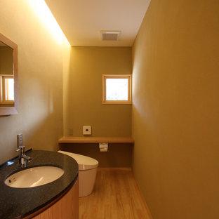 Diseño de aseo de estilo zen, pequeño, con armarios con rebordes decorativos, puertas de armario de madera clara, sanitario de una pieza, paredes beige, suelo de madera clara, lavabo bajoencimera, encimera de granito, suelo beige y encimeras negras