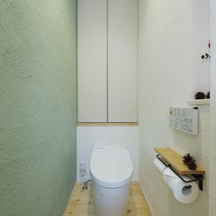 Diseño de aseo escandinavo con sanitario de una pieza, paredes verdes y suelo de madera clara