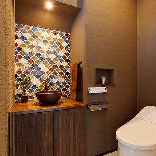 На фото: туалет в восточном стиле с темными деревянными фасадами, унитазом-моноблоком, разноцветной плиткой, коричневыми стенами, столешницей из дерева, бежевым полом и коричневой столешницей с