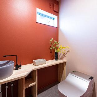 Modelo de aseo asiático con parades naranjas, lavabo sobreencimera, encimera de madera, suelo gris y encimeras marrones