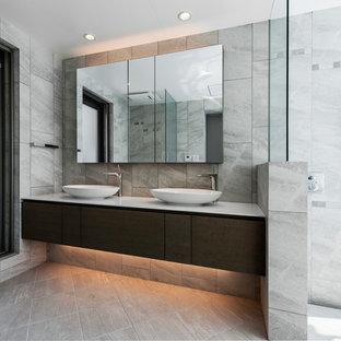 Идея дизайна: туалет в современном стиле с темными деревянными фасадами, серой плиткой, серыми стенами, накладной раковиной, серым полом и плоскими фасадами
