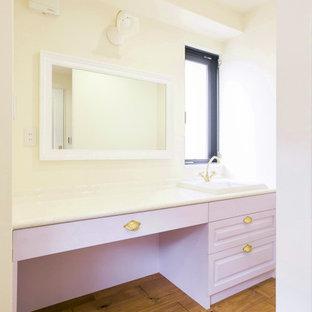 Cette photo montre un WC et toilettes chic avec un placard avec porte à panneau surélevé, des portes de placard violettes, un mur beige, un sol en bois foncé, un lavabo posé, un plan de toilette en marbre et un sol marron.