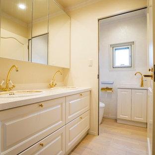 東京23区のトラディショナルスタイルのおしゃれなトイレ・洗面所 (レイズドパネル扉のキャビネット、白いキャビネット、白い壁、塗装フローリング、オーバーカウンターシンク、ベージュの床) の写真