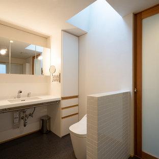 他の地域のモダンスタイルのおしゃれなトイレ・洗面所 (白いキャビネット、一体型トイレ、白いタイル、セラミックタイル、白い壁、クッションフロア、アンダーカウンター洗面器、人工大理石カウンター、グレーの床、白い洗面カウンター) の写真