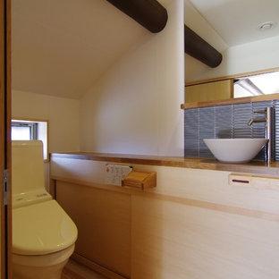 На фото: туалеты в восточном стиле с фасадами с декоративным кантом, светлыми деревянными фасадами, унитазом-моноблоком, синей плиткой, стеклянной плиткой, белыми стенами, светлым паркетным полом, настольной раковиной и столешницей из дерева