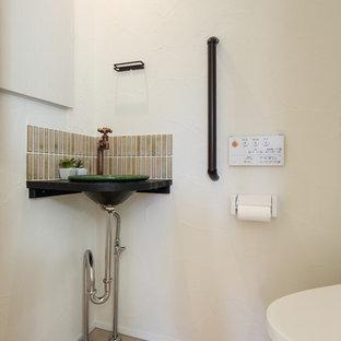 Diseño de aseo asiático, pequeño, con sanitario de una pieza, baldosas y/o azulejos blancos, paredes blancas, suelo de corcho, lavabo sobreencimera, encimera de madera, suelo marrón y encimeras marrones