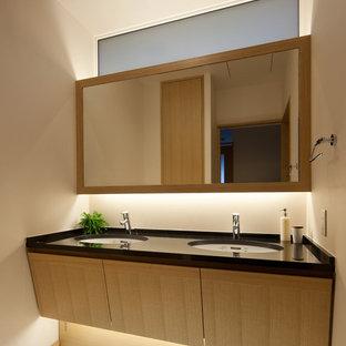 Esempio di un bagno di servizio etnico con pareti beige, lavabo da incasso e pavimento bianco