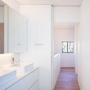 大阪の小さいコンテンポラリースタイルのおしゃれなトイレ・洗面所 (白いキャビネット、白い壁、オーバーカウンターシンク、人工大理石カウンター、白い洗面カウンター、フラットパネル扉のキャビネット、無垢フローリング、茶色い床) の写真