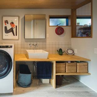 Cette photo montre un WC et toilettes industriel avec un placard sans porte, des portes de placard en bois brun, un mur blanc, un sol en bois peint, une vasque, un plan de toilette en bois et un sol gris.
