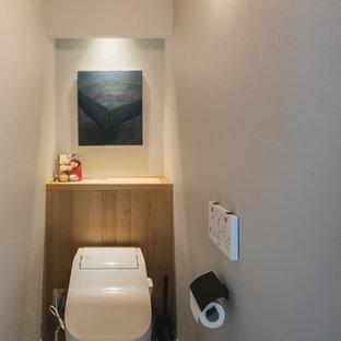 Новые идеи обустройства дома: туалет в скандинавском стиле с белыми стенами, деревянным полом и серым полом