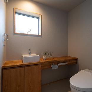 Idées déco pour un WC et toilettes asiatique avec un placard à porte affleurante, des portes de placard en bois brun, un mur bleu, un plan de toilette en bois, un sol blanc et un plan de toilette marron.