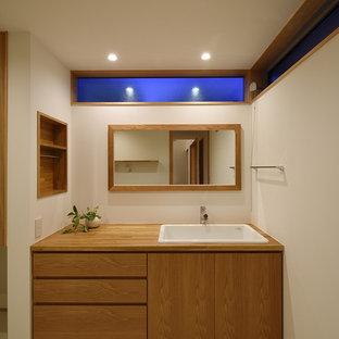 他の地域の北欧スタイルのおしゃれなトイレ・洗面所 (中間色木目調キャビネット、白い壁、木製洗面台、ブラウンの洗面カウンター、オーバーカウンターシンク、ベージュの床) の写真
