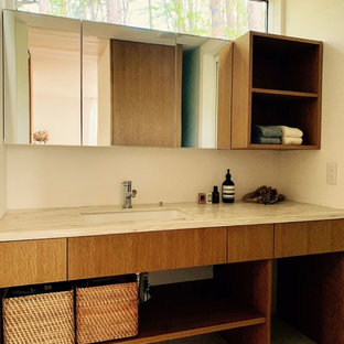 Imagen de aseo de estilo zen con armarios abiertos, puertas de armario con efecto envejecido, paredes blancas, lavabo integrado y suelo beige