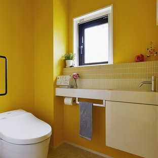 Moderne Gästetoilette mit weißen Schränken, Toilette mit Aufsatzspülkasten, gelben Fliesen, gelber Wandfarbe und integriertem Waschbecken in Tokio
