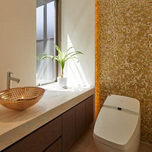 Réalisation de WC et toilettes minimalistes avec un placard à porte plane, des portes de placard grises, un carrelage jaune, un mur blanc, une vasque, un sol marron et un plan de toilette beige.