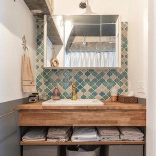 東京23区のインダストリアルスタイルのおしゃれなトイレ・洗面所 (オープンシェルフ、ヴィンテージ仕上げキャビネット、マルチカラーの壁、無垢フローリング、オーバーカウンターシンク、木製洗面台、茶色い床、ブラウンの洗面カウンター) の写真