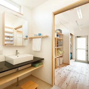 На фото: туалеты в восточном стиле с открытыми фасадами, белыми стенами, настольной раковиной и серым полом