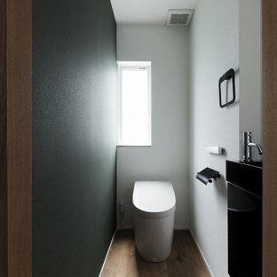 他の地域のおしゃれなトイレ・洗面所 (緑の壁、木目調タイルの床、茶色い床、クロスの天井、壁紙) の写真